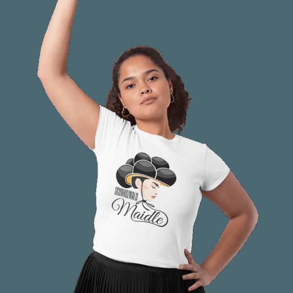 frau mit einem arm an der huefte und einem arm in der hoehe traegt weisses tshirt mit motiv schwarzwaldmaidle kristin