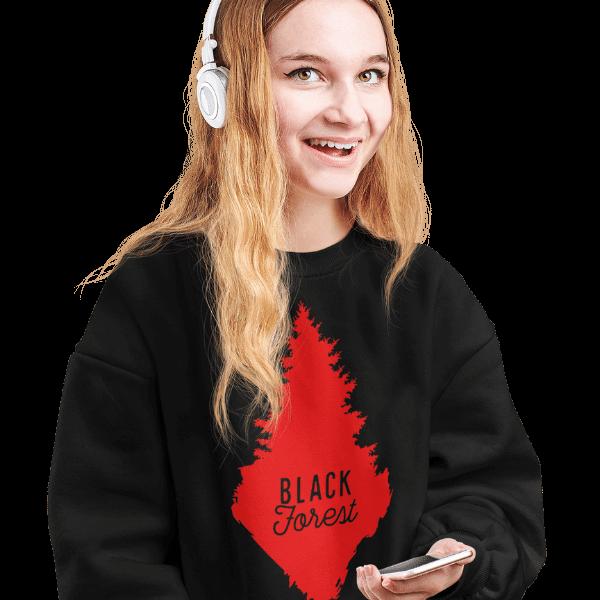 blonde frau im studio mit kopfhoerern und schwarzem pulli mit rote schwarzwald tanne design