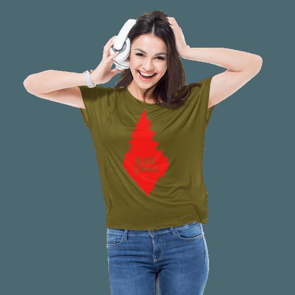 fraue im studio mit gruenem t-shirt mit design rote schwarzwald tanne