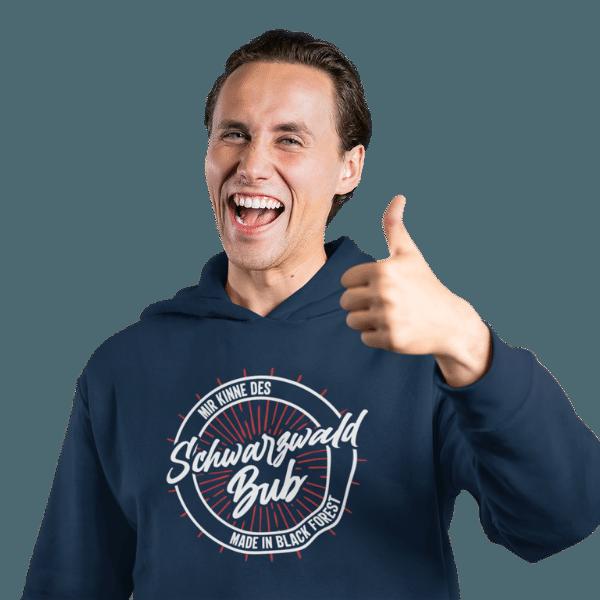 froehlicher mann macht das ok zeichen mit blauem hoodie mit schwarzwald bub motiv