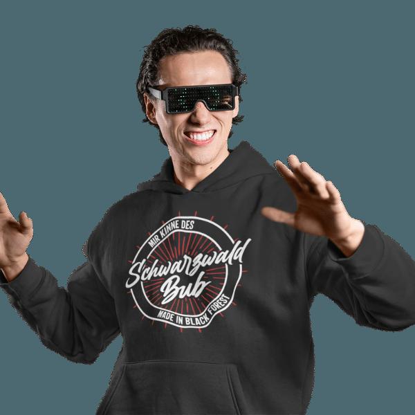 mann mit brille und grauem hoodie mit motiv schwarzwald bub (mir kinne des)