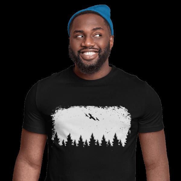 gluecklicher mann im studio mit schwarzem t-shirt mit motiv black forest wildness