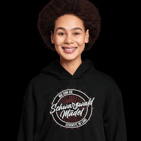 froehliche frau im studio mit schwarzem hoodie mit motiv schwarzwald maedel
