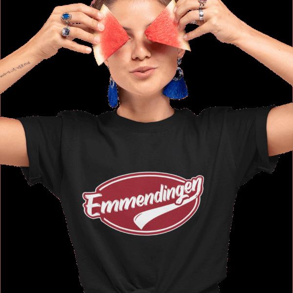 frau bedeckt ihre augen mit stuecken einer wassermelone die ein schwarzes t-shirt traegt mit emmendingen design