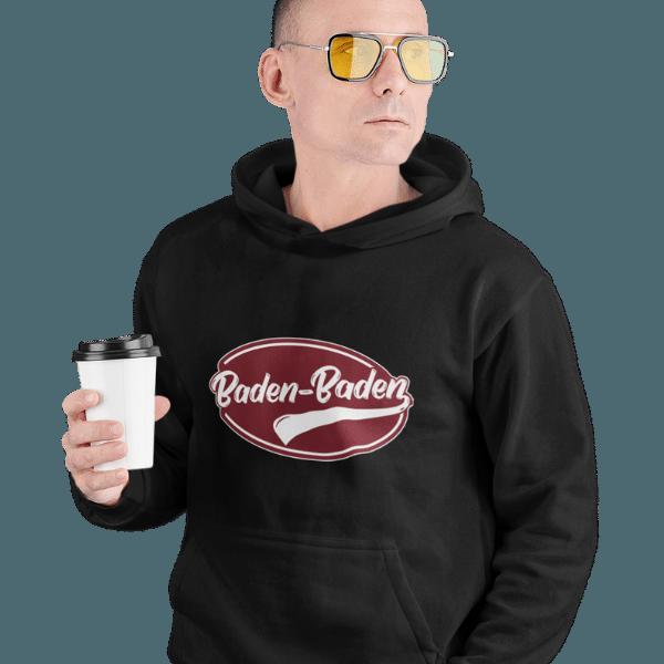 mann mit kaffee und brille mit schwarzem hoodie mit aufdruck baden-baden