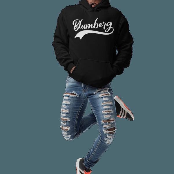 mann springend im studio mit schwarzem hoodie mit blumberg design
