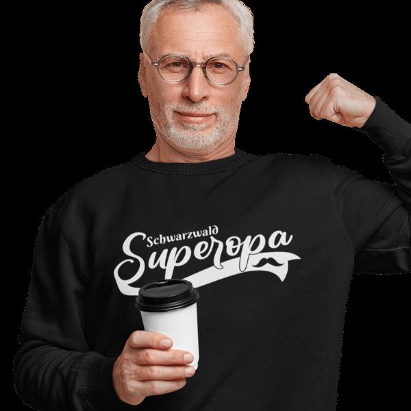 grauhaariger mann mit brille und kaffee mit schwarzem sweatshirt mit aufdruck schwarzwald super opa