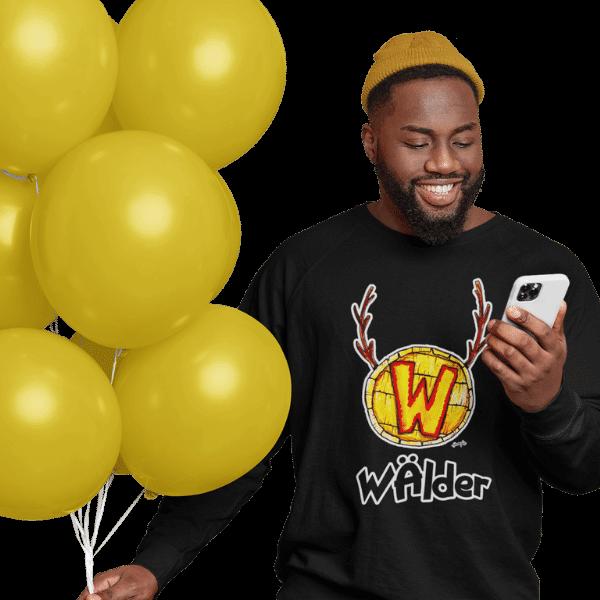 mann mit luftballoons und handy im studio mit schwarzem tshirt mit waelder hochschwarzwald design