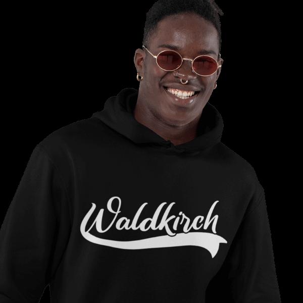 gluecklicher mann mit sonnenbrille im studio mit schwarzem tshirt mit waldkirch design