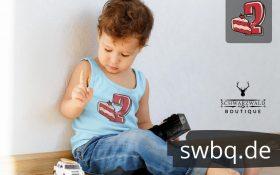 kleiner junge spielend auf dem boden sitzend mit hellblauem tank top mit aufdruck 2. geburtstag schwarzwald