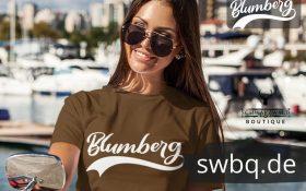 frau mit brille und braunem t-shirt mit blumberg logo