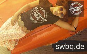 frau mit braunem tshirt liegend mit sonnebrille mit design schwarzwald maedel