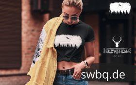 blonde frau auf der strasse mit kurzem schwarzem tshirt mit black forest wildness motiv