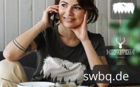frau mit telefon und schwarzem t-shirt mit black forest wildness design