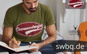 mann schreibend auf dem bett mit gruenem t-shirt mit donaueschingen design