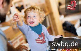 kleiner blonder junge mit hellblauem langarm t-shirt mit 2. geburtstag schwarzwald design