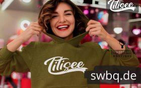 glueckliche frau mit gruenem hoodie mit motiv titisee