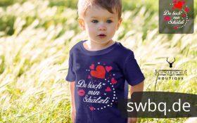 kleines kind auf der wiese mit blauem t-shirt mit schwarzwald schaetzli aufdruck