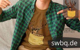 mann auf dem sofa sitzend mit braunem shirt mit schwarzwaelder hirschtaeschle logo