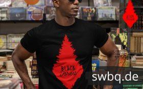 mann mit sonnenbrille in einem schallplatten laden mit tshirt mit desing rote schwarzwald tanne