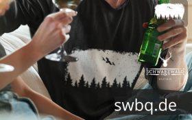 mann trinkt mit freunden mit schwarzem tshirt mit balck forest wildness design