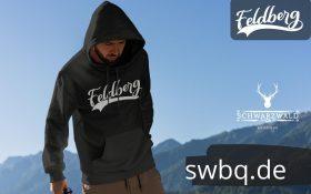 mann in den bergen mit grauem hoodie mit feldberg design