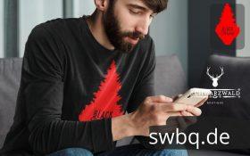mann mit handy und schwarzem t-shirt mit rote schwarzwald tanne design