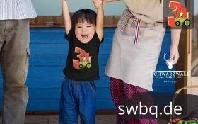 eltern mit kleinem kind das ein schwarzes t-shirt mit 2. geburtstag schwarwald design traegt