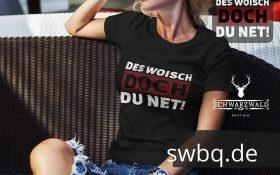 frau auf einem sofa mit schwarzem t-shirt mit des woisch doch du net design