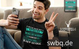mann auf dem sofa mit handy und schwarzem t-shirt mit alemannisch raus gugge design