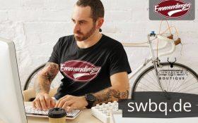 mann mit bart am schreibtisch mit schwarzem t-shirt mit design emmendingen