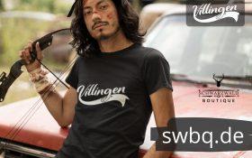 mann mit boden vor einem auto mit schwarzem tshirt mit villingen design