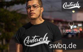 mann mit brille und tatoos mit schwarzem t-shirt mit gutach motiv