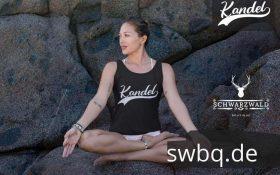 frau sitzen auf steinen in einer yoga pose mit schwarzem tank top mit kandel