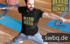 mann beim yoga mit schwarzem t-shirt mit motiv badisch bleed gschwaetzt