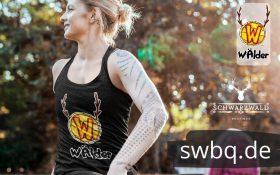 frau in yoga pose im freien mit einem schwarzen tank top mit logo waelder hochschwarzwald