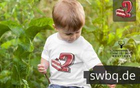 kleiner junge auf der wiese mit weissem t-shirt mit 2. geburtstag schwarzwald motiv